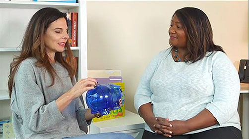 Gail holds a piggy bank and explains emotions to Dawn, the host